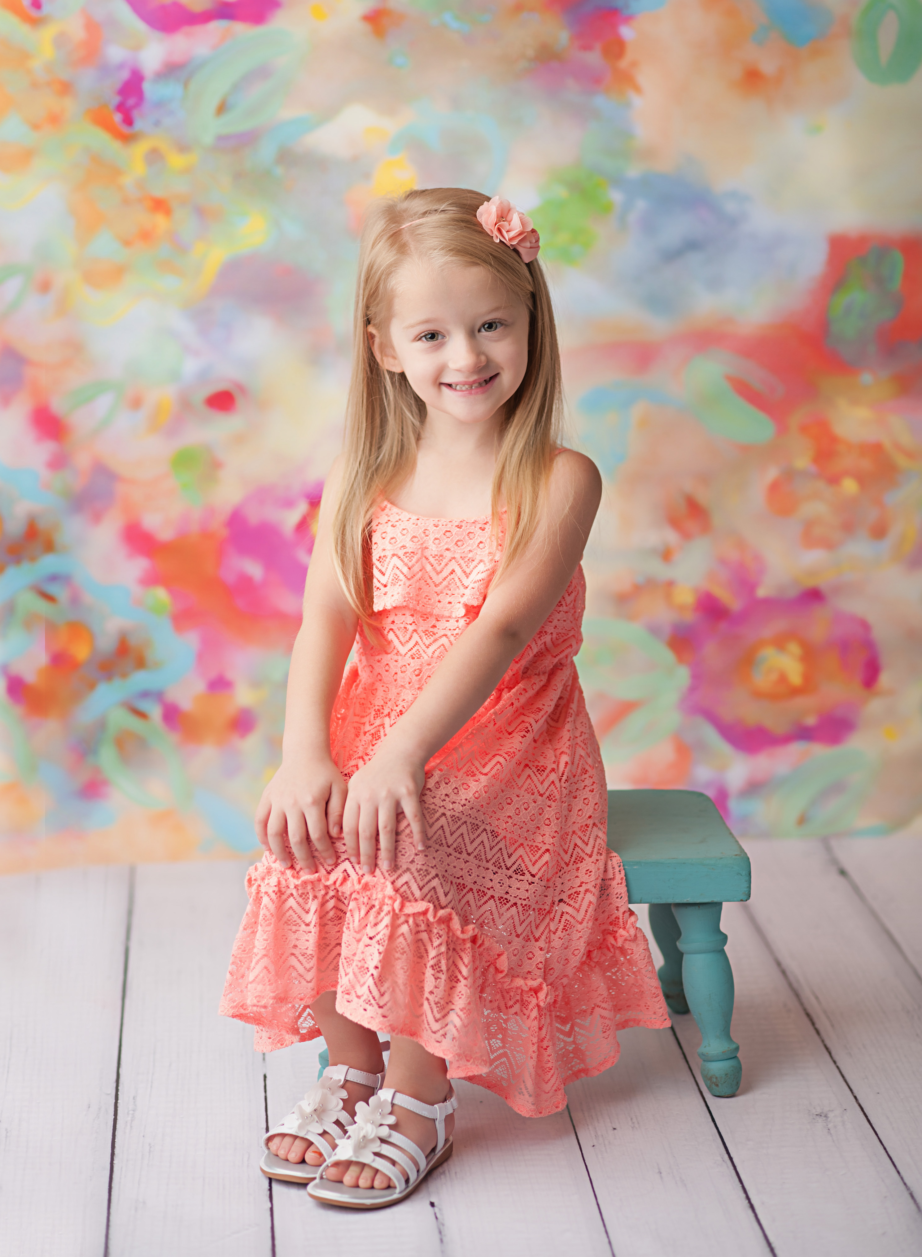 girl in dress on floral backdrop