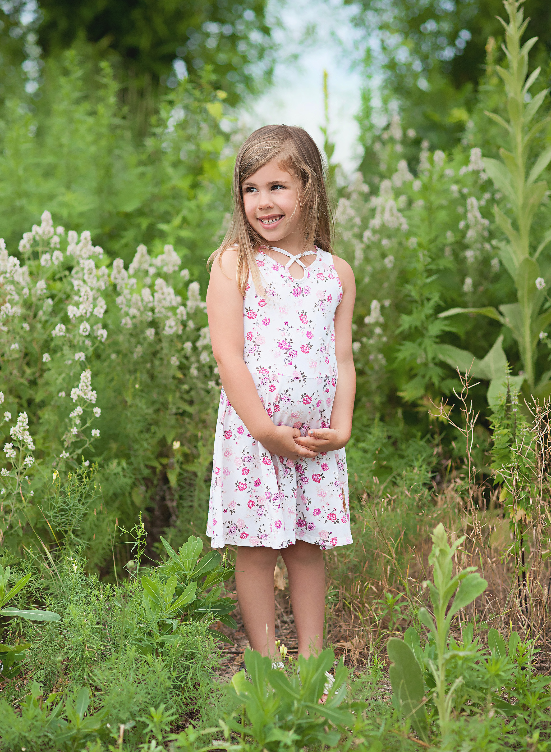 little girl standing in tall grass