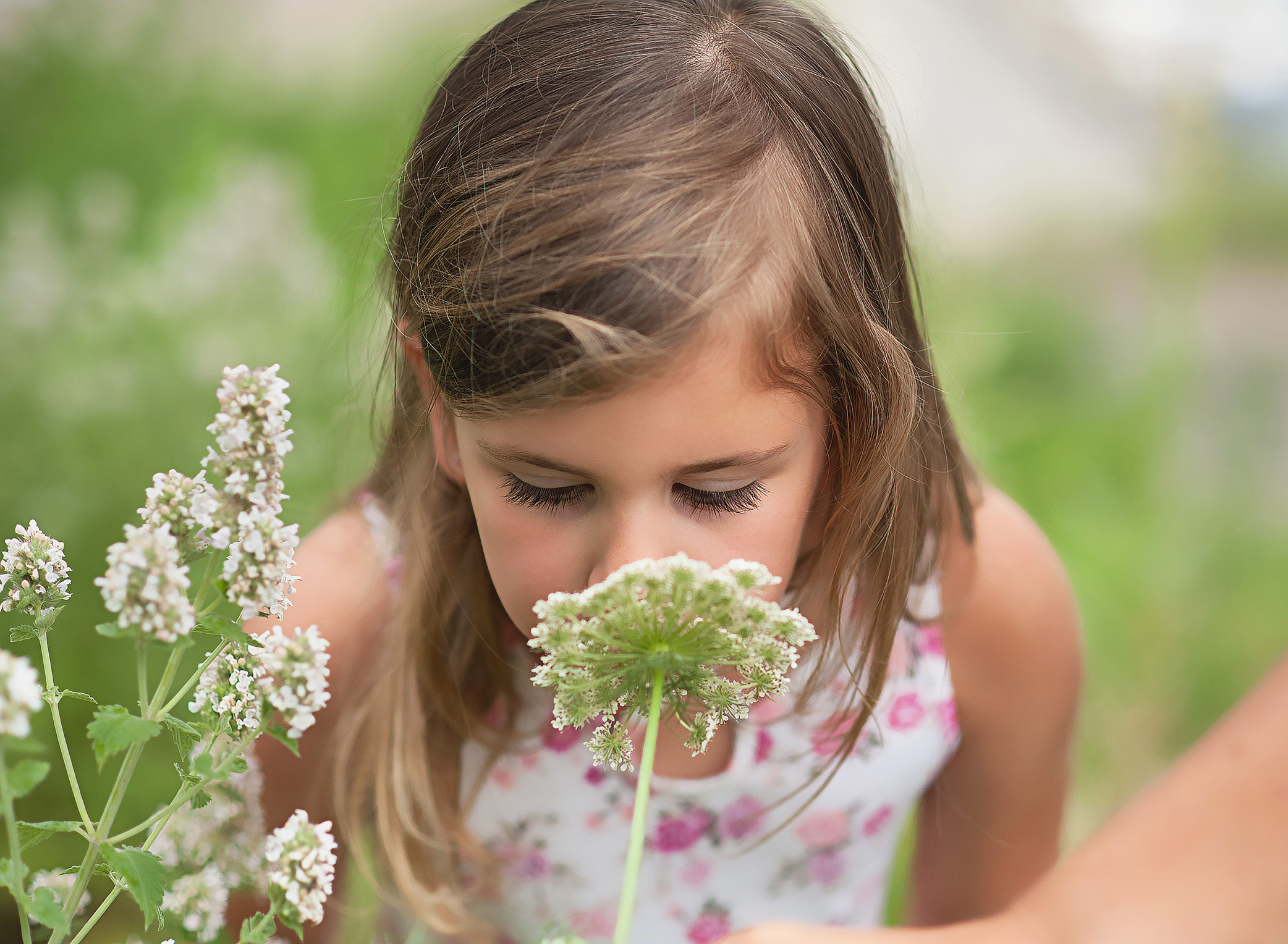 little girl smelling a wildflower