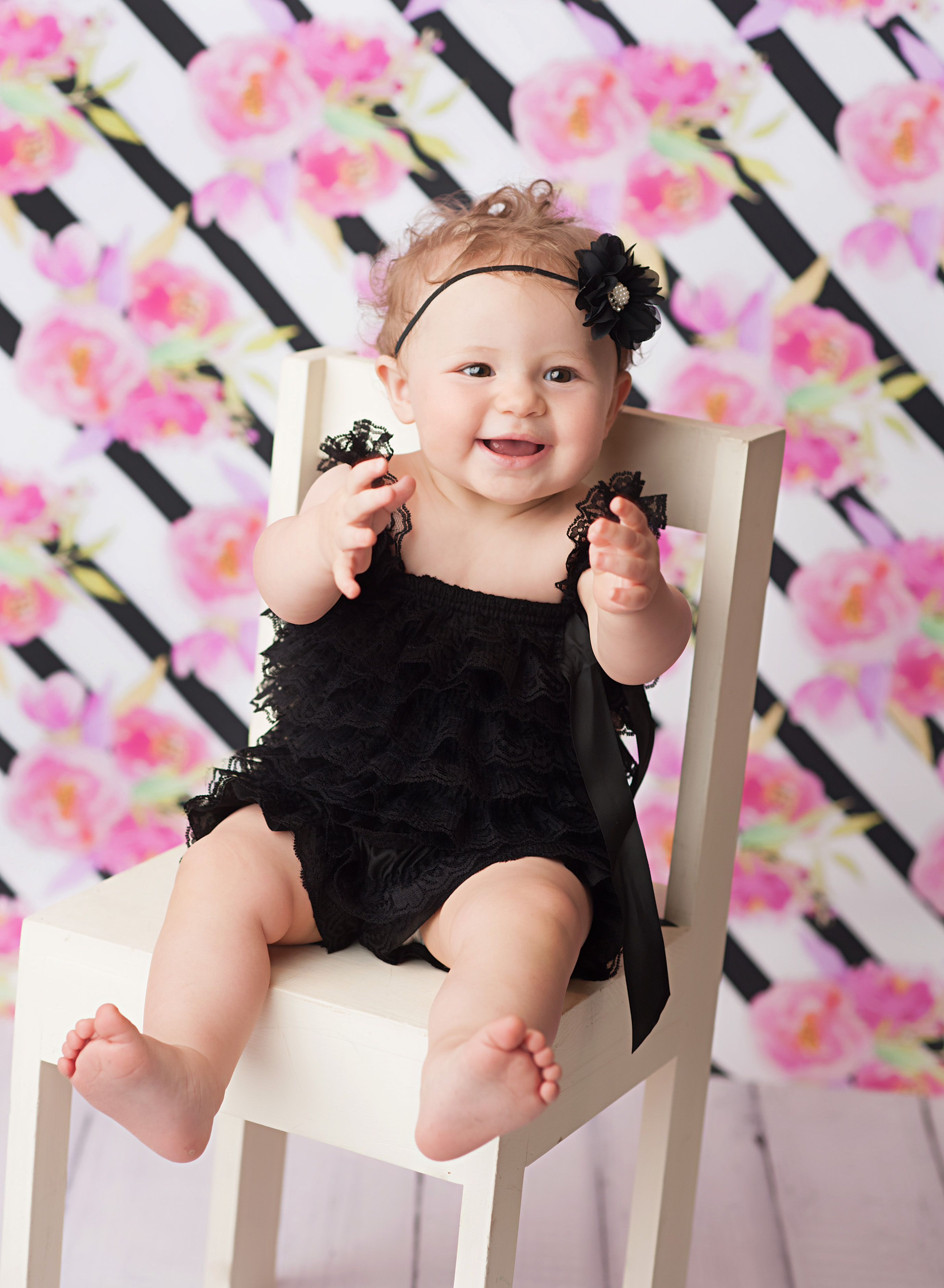 baby on chair in front of floral backdrop