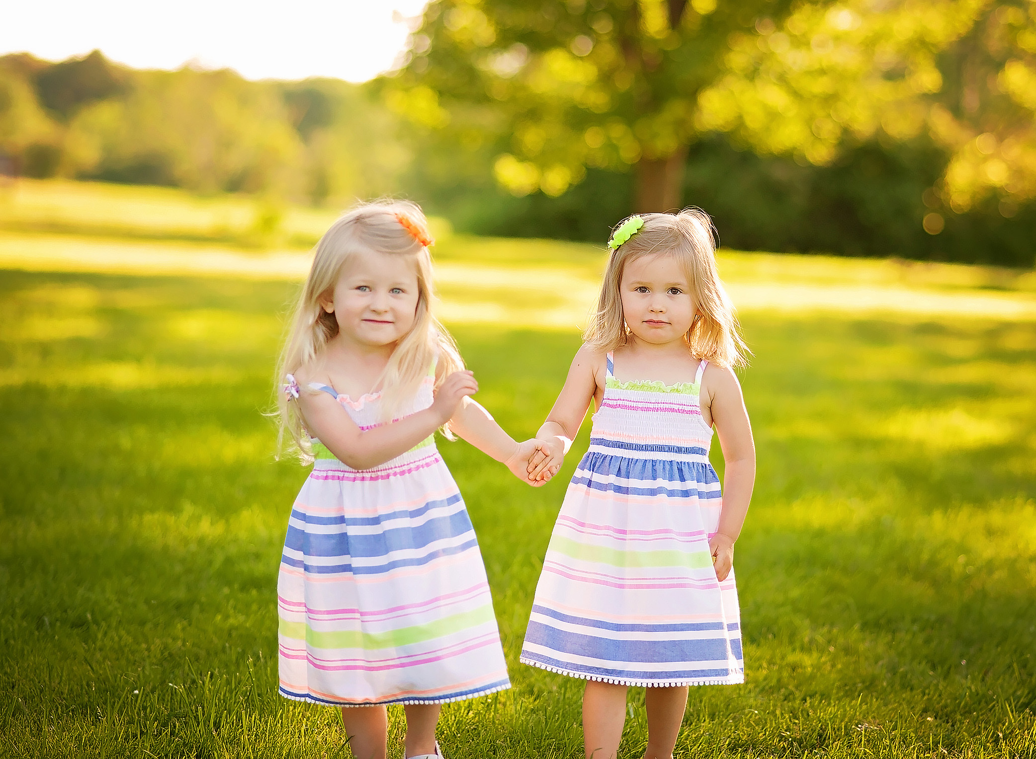 twin girls holding hands in the sunlight