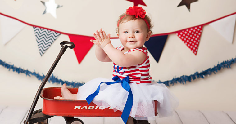 baby in wagon on patriotic backdrop