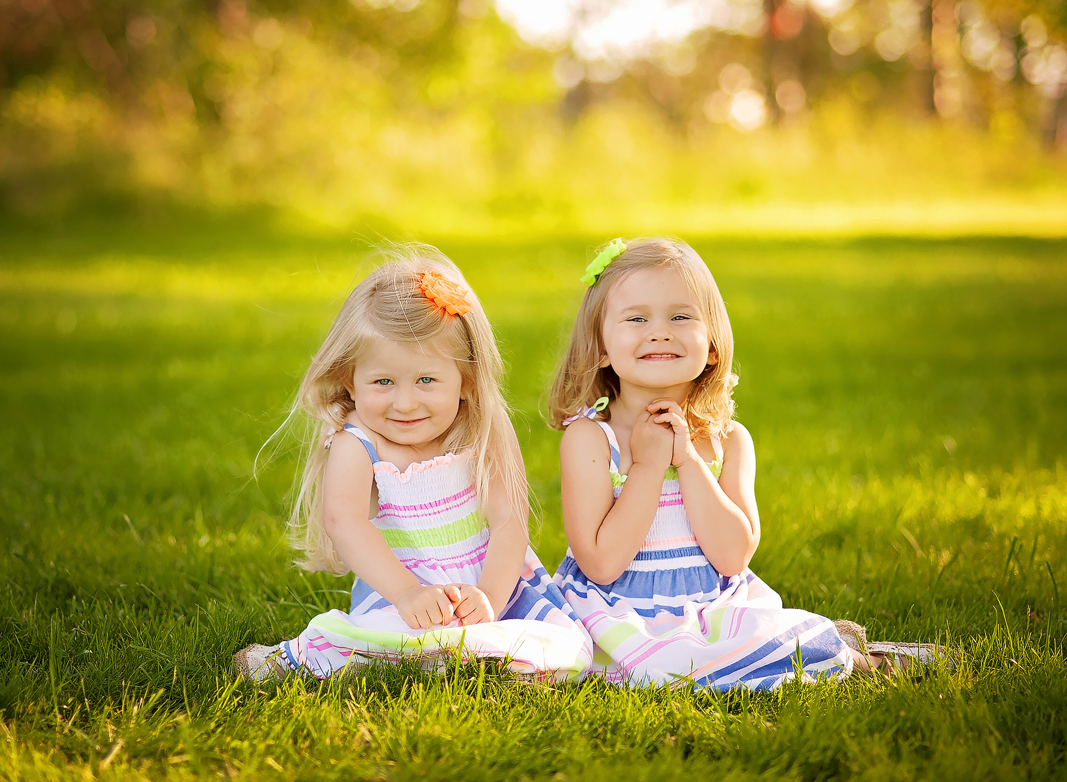twin girls sitting in a field