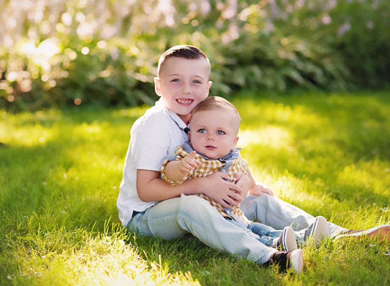 brothers hugging in the grass