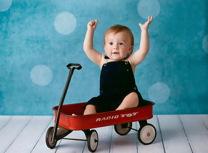 boy in overalls in red wagon