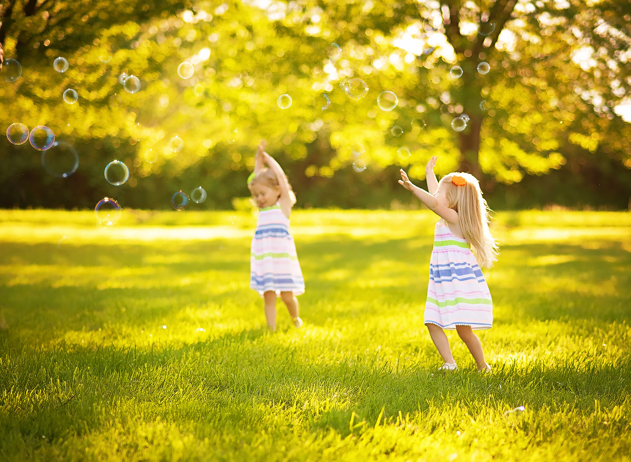 twin girls catching bubbles in a field