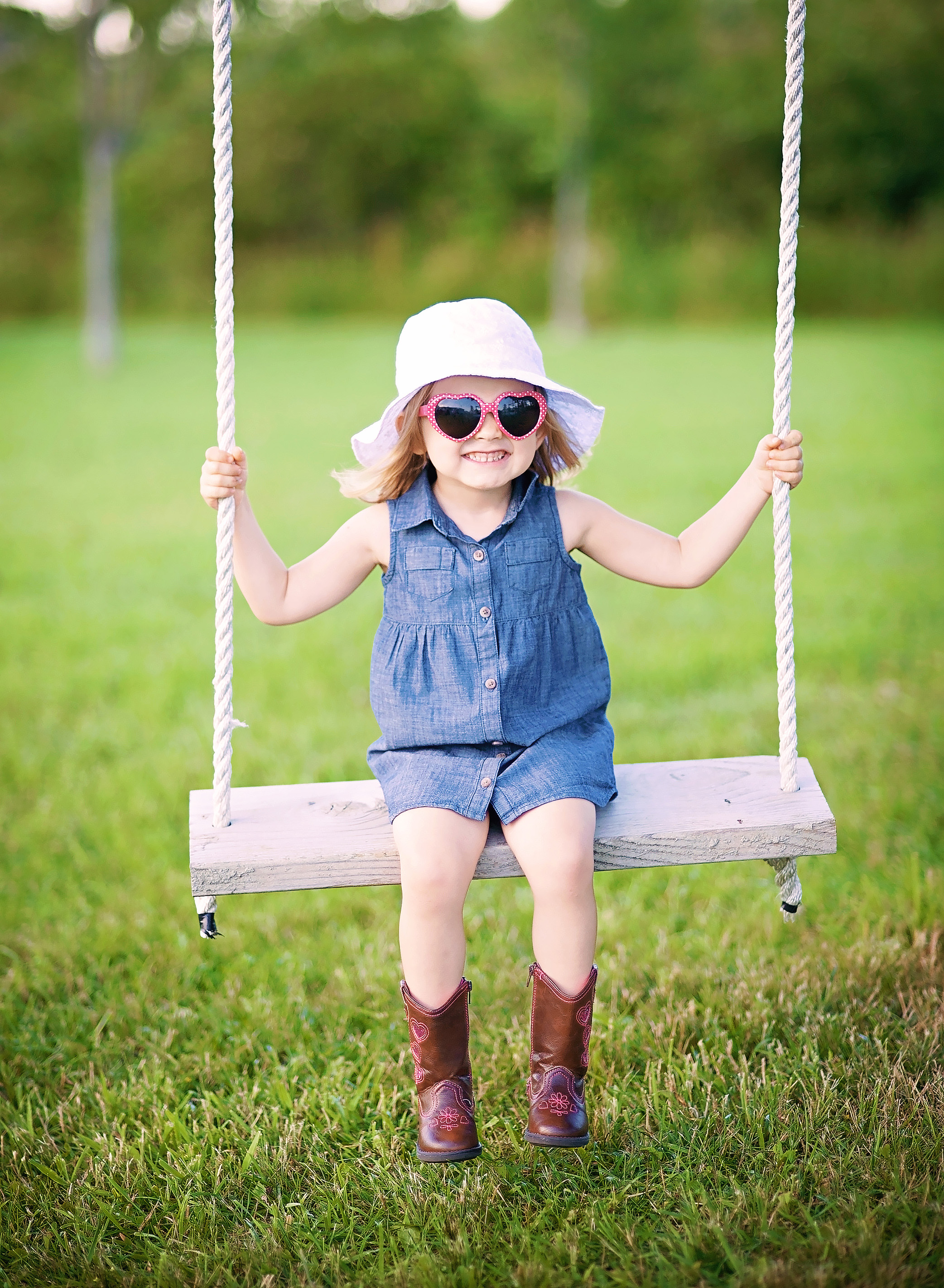 little girl in sunglasses on a swing