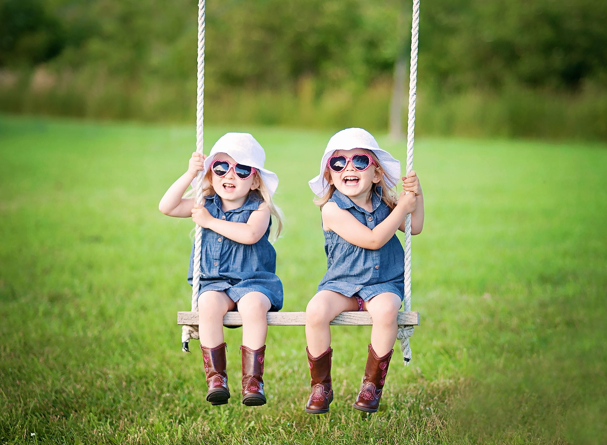 twin girls in sunglasses on a swing