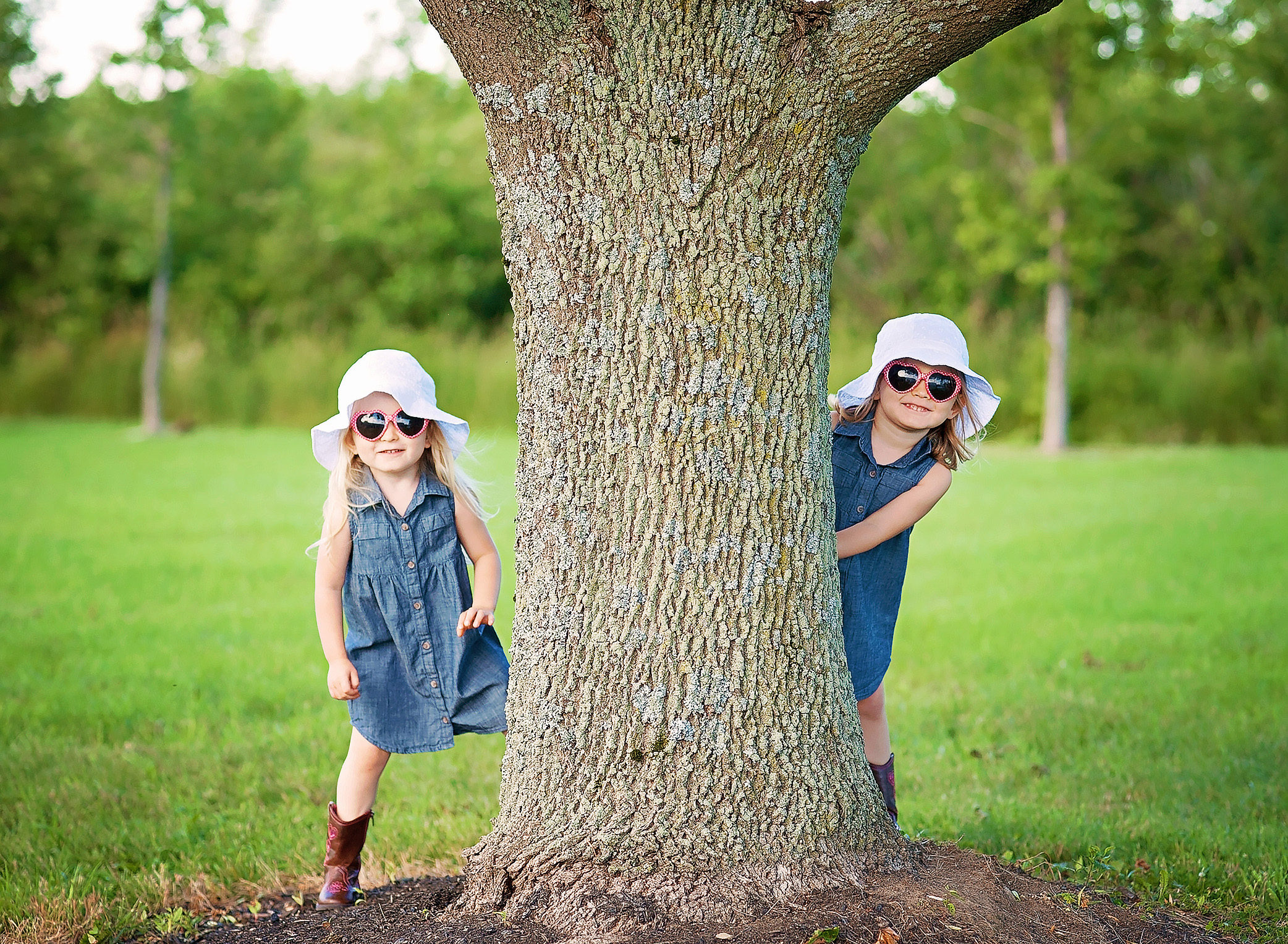 twin girls hiding behind a tree