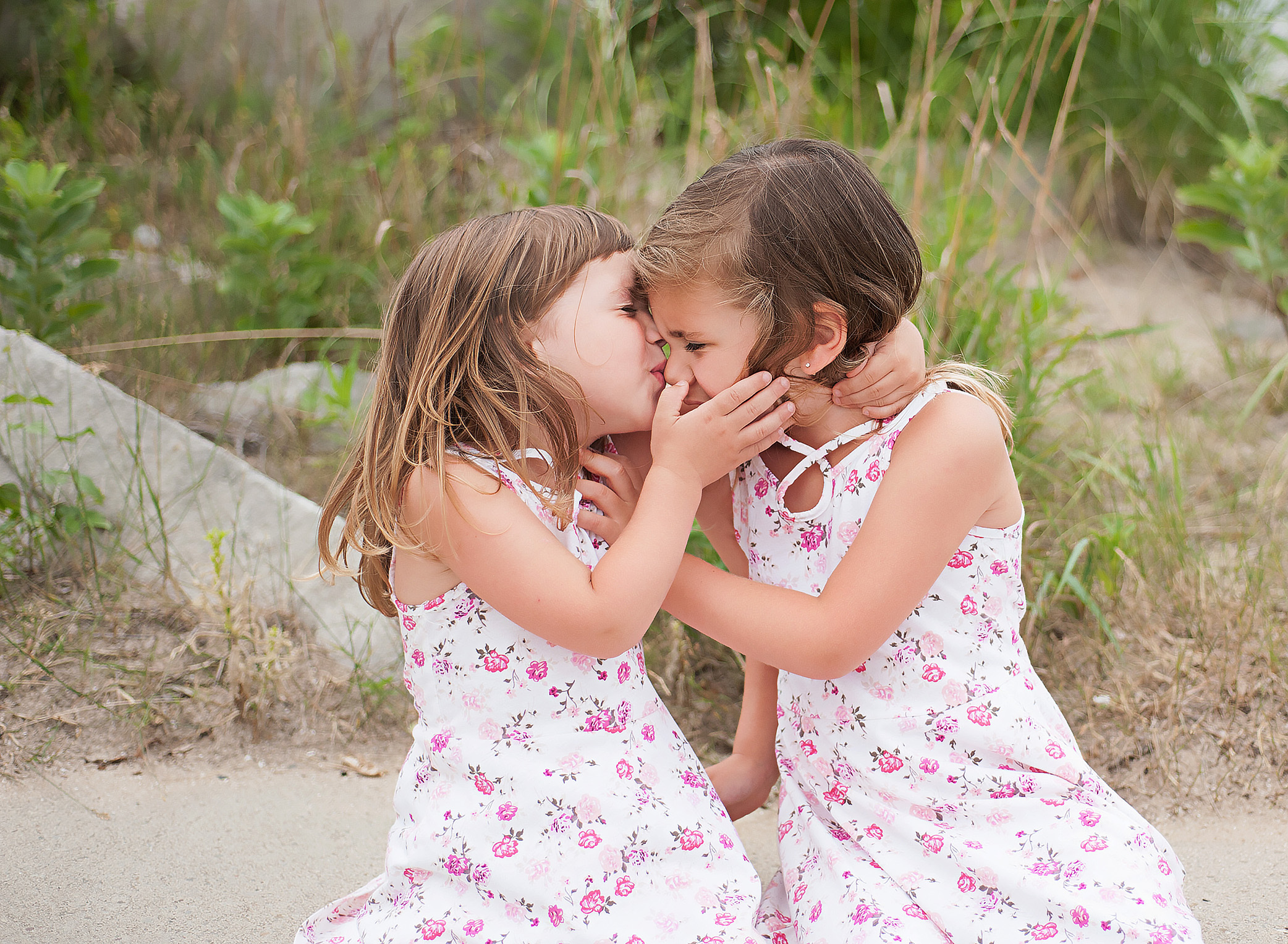 sisters kissing at the beach