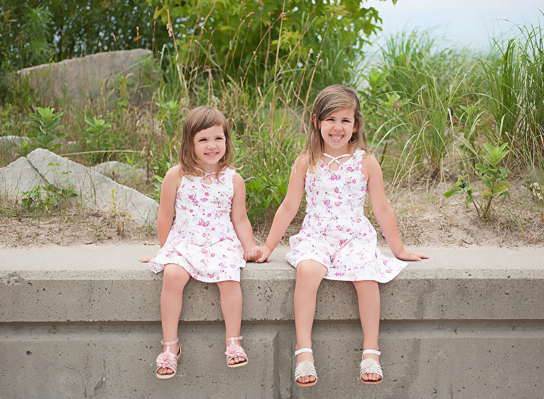 little girls sitting on a wall at the beach