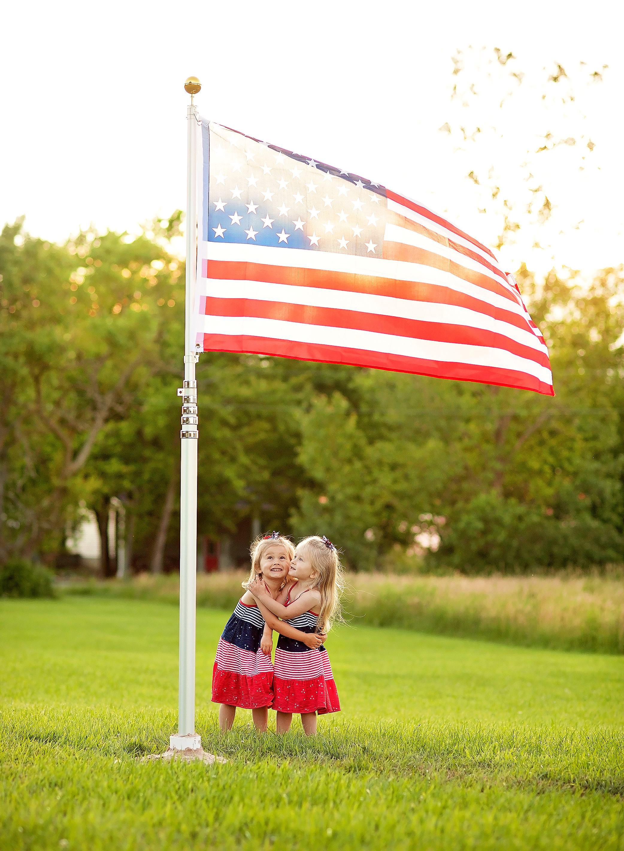 twin girls hugging under american flag