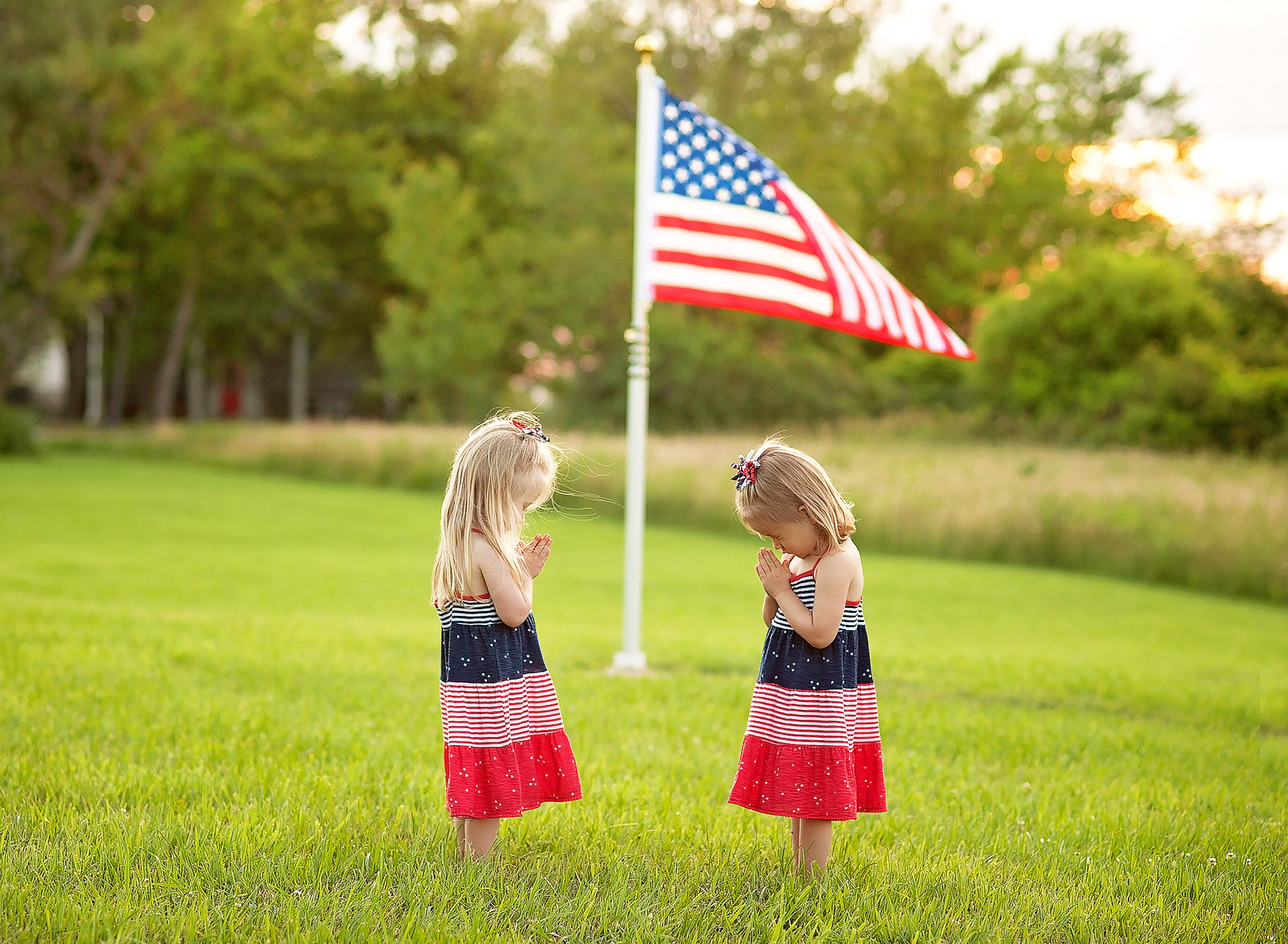 twin grls praying under american flag