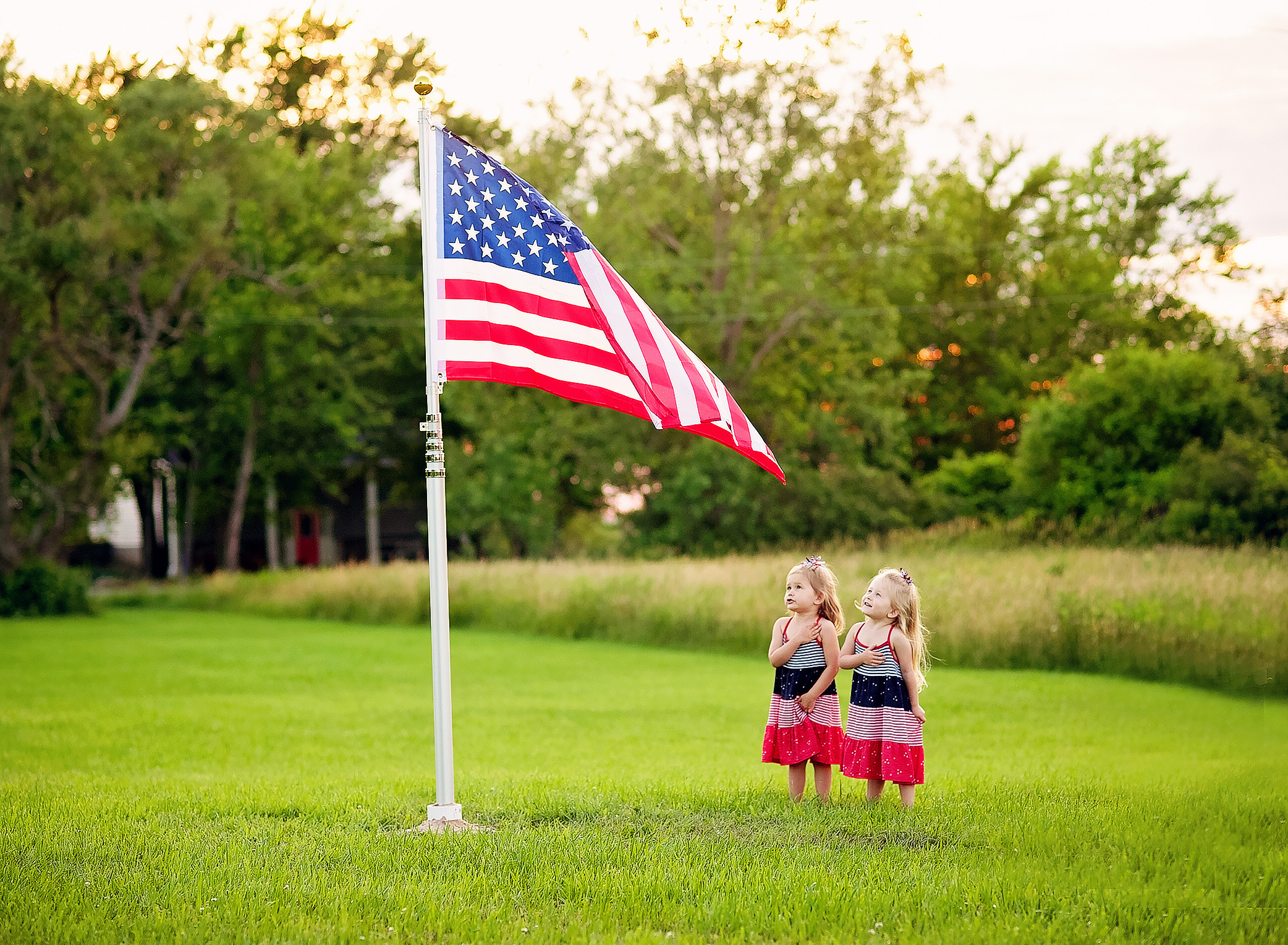twin girls saying the pledge under american flag