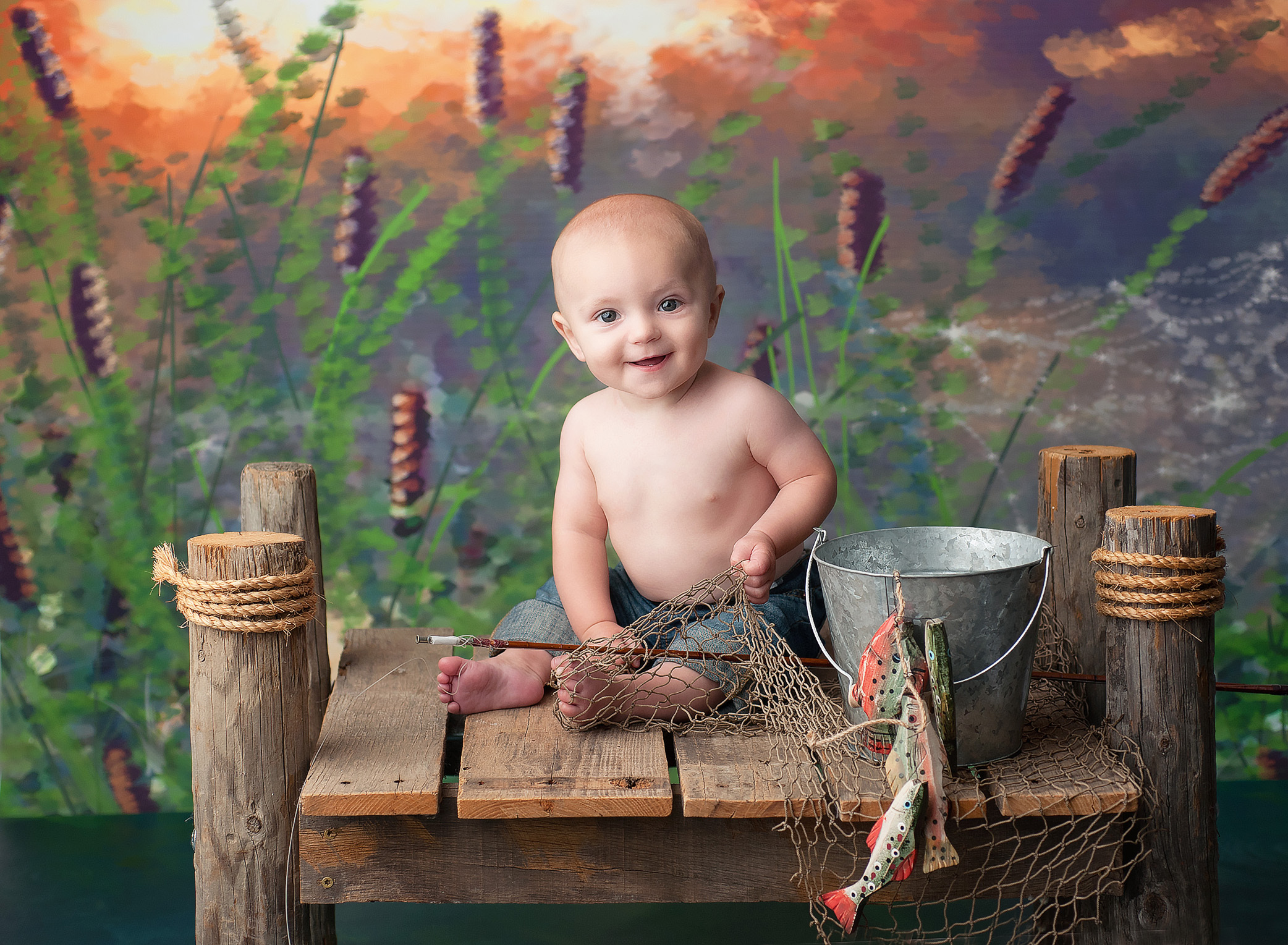 baby boy sitting on a dock fishing