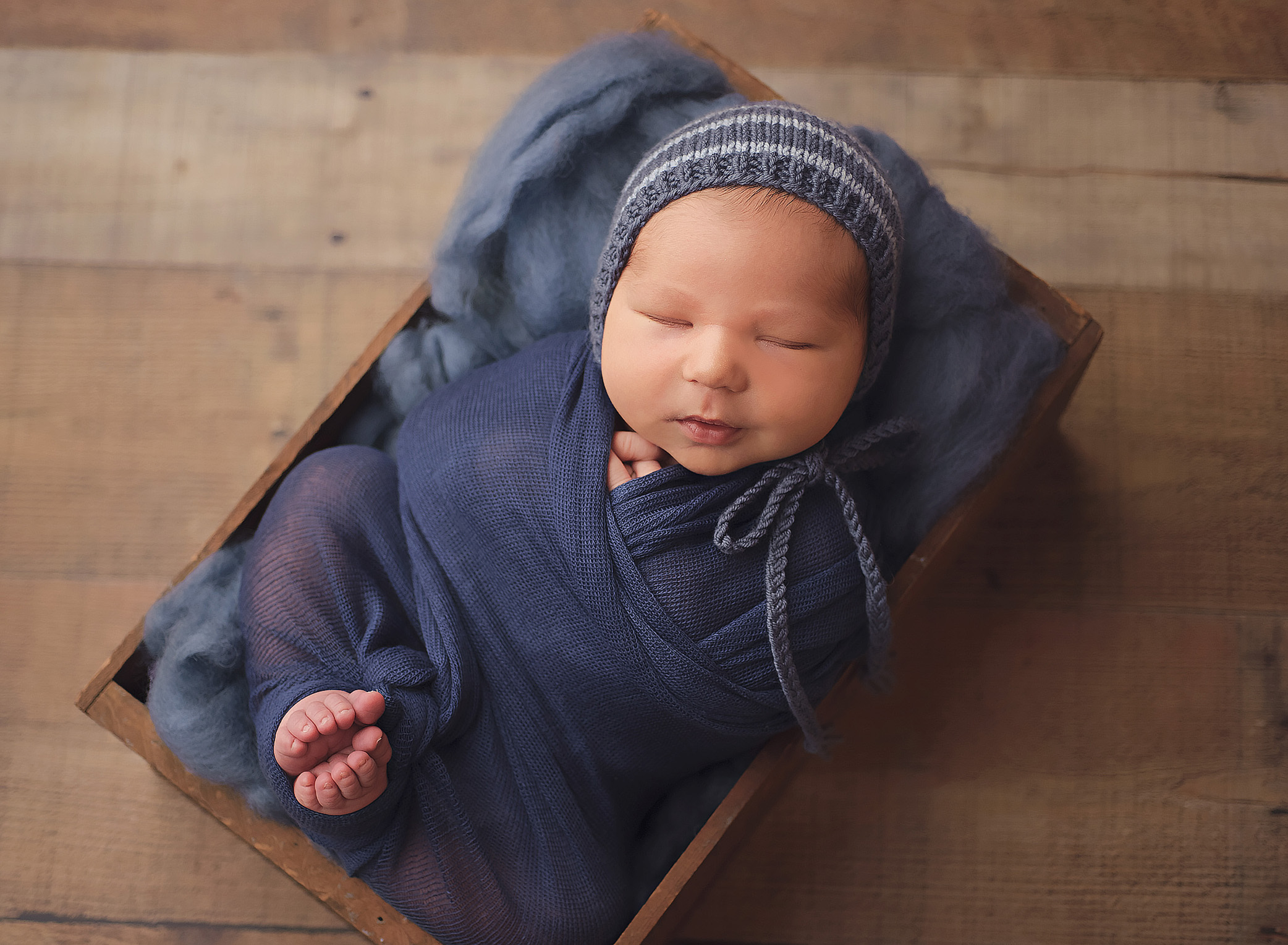 newborn baby in blue wrap