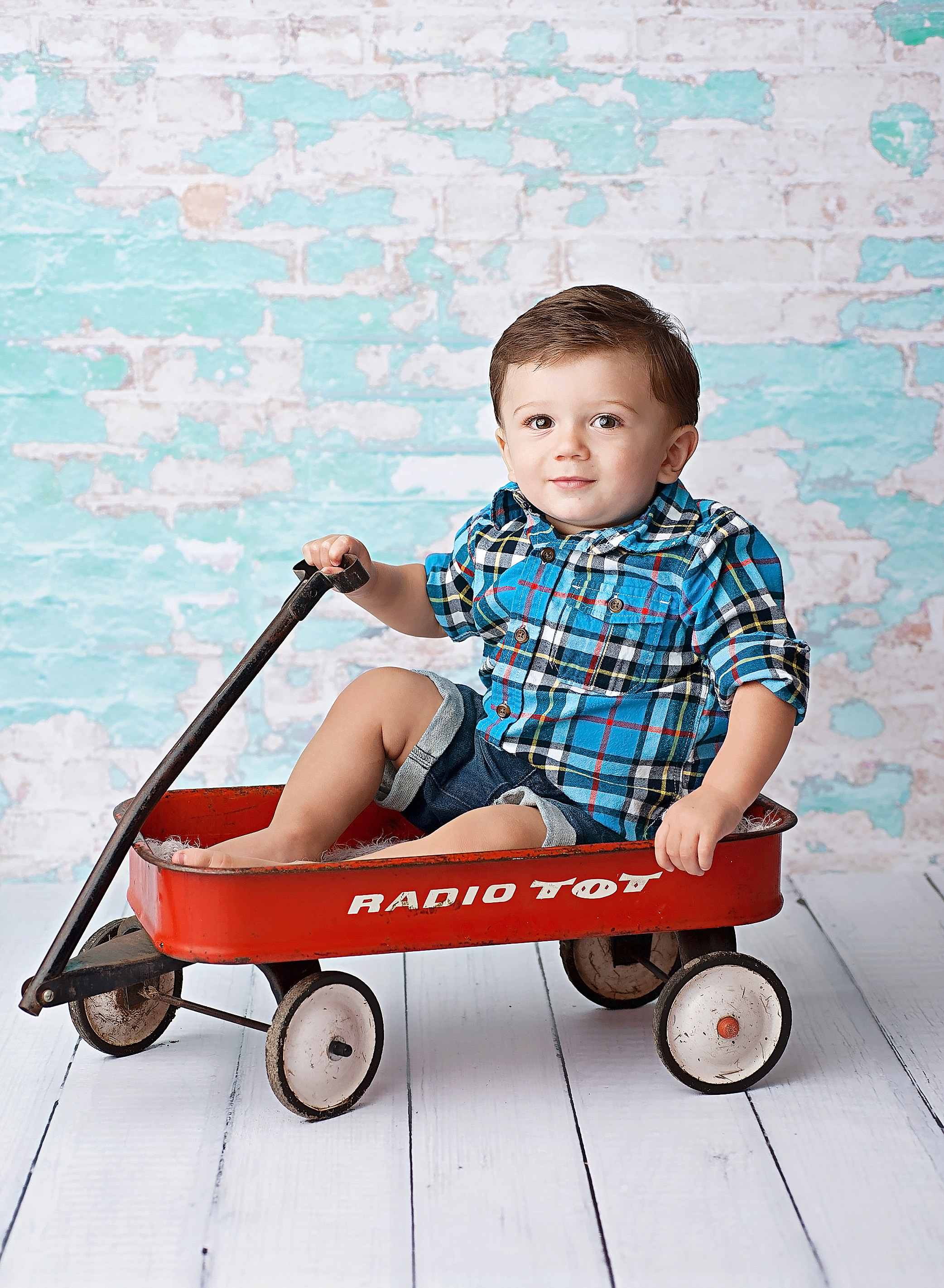 boy sitting in red wagon