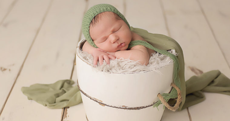 newborn boy in white bucket and green wrap