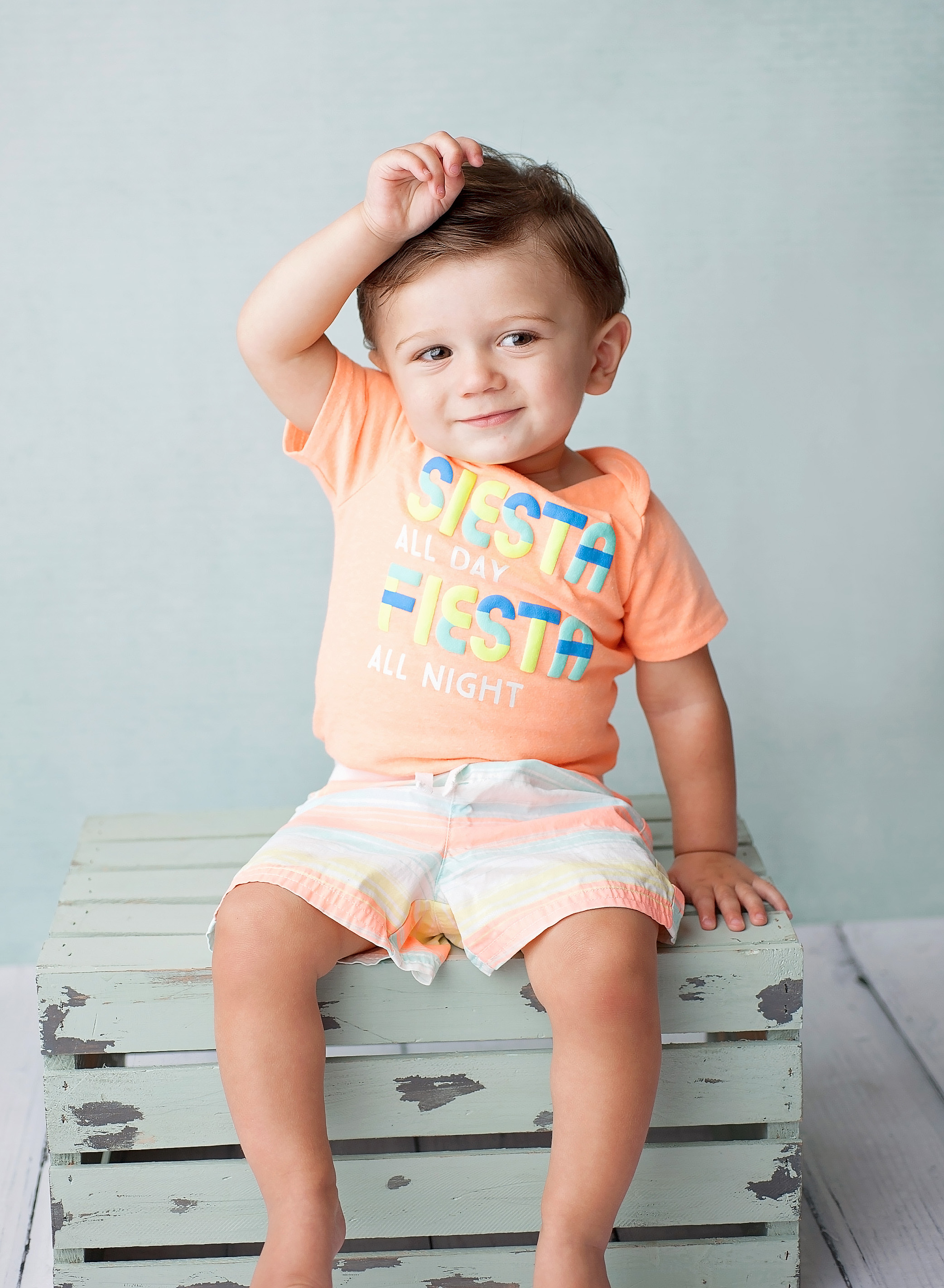 boy with orange shirt on sitting on blue stool