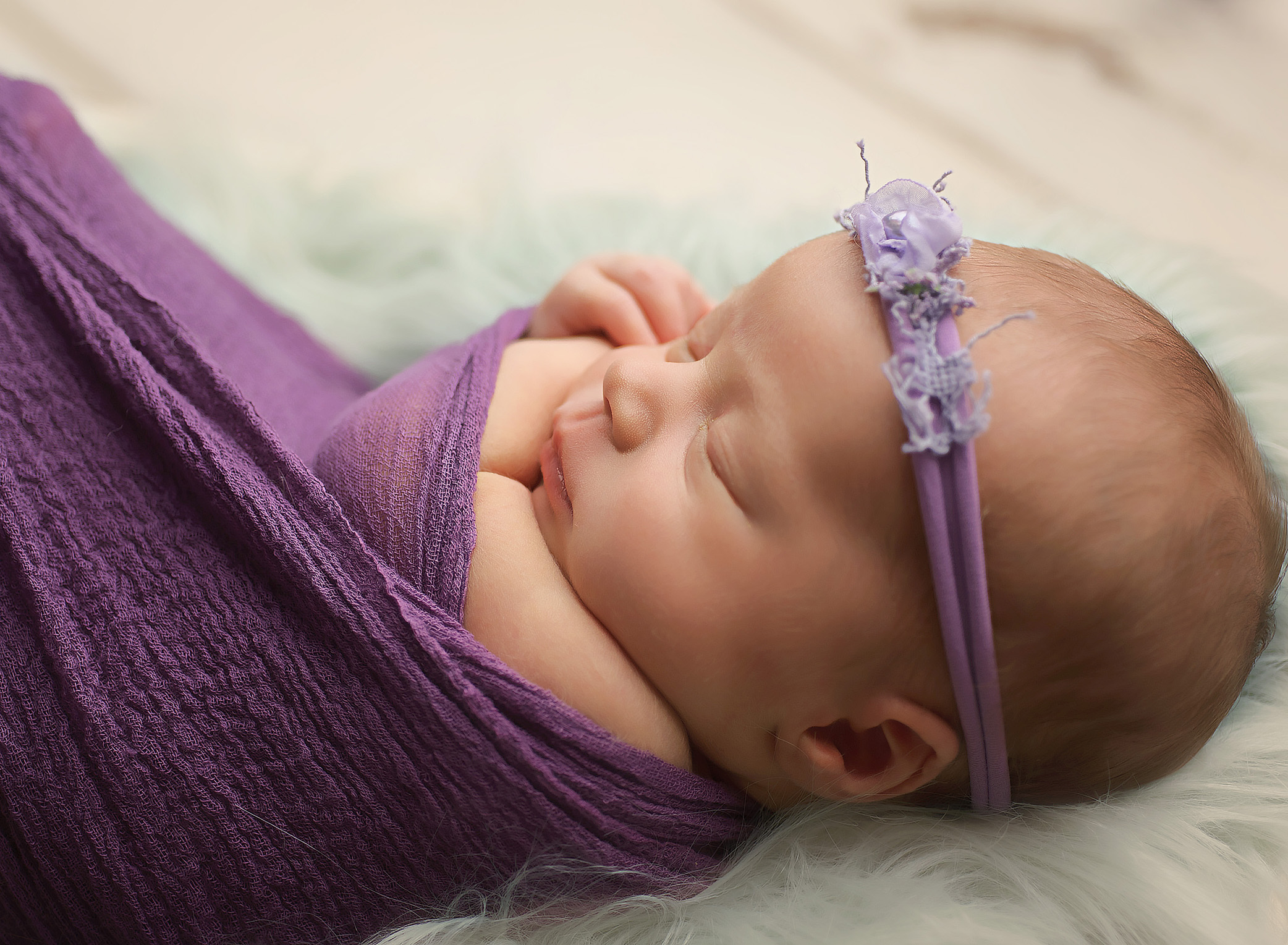 baby girl wrapped in purple on mint fur