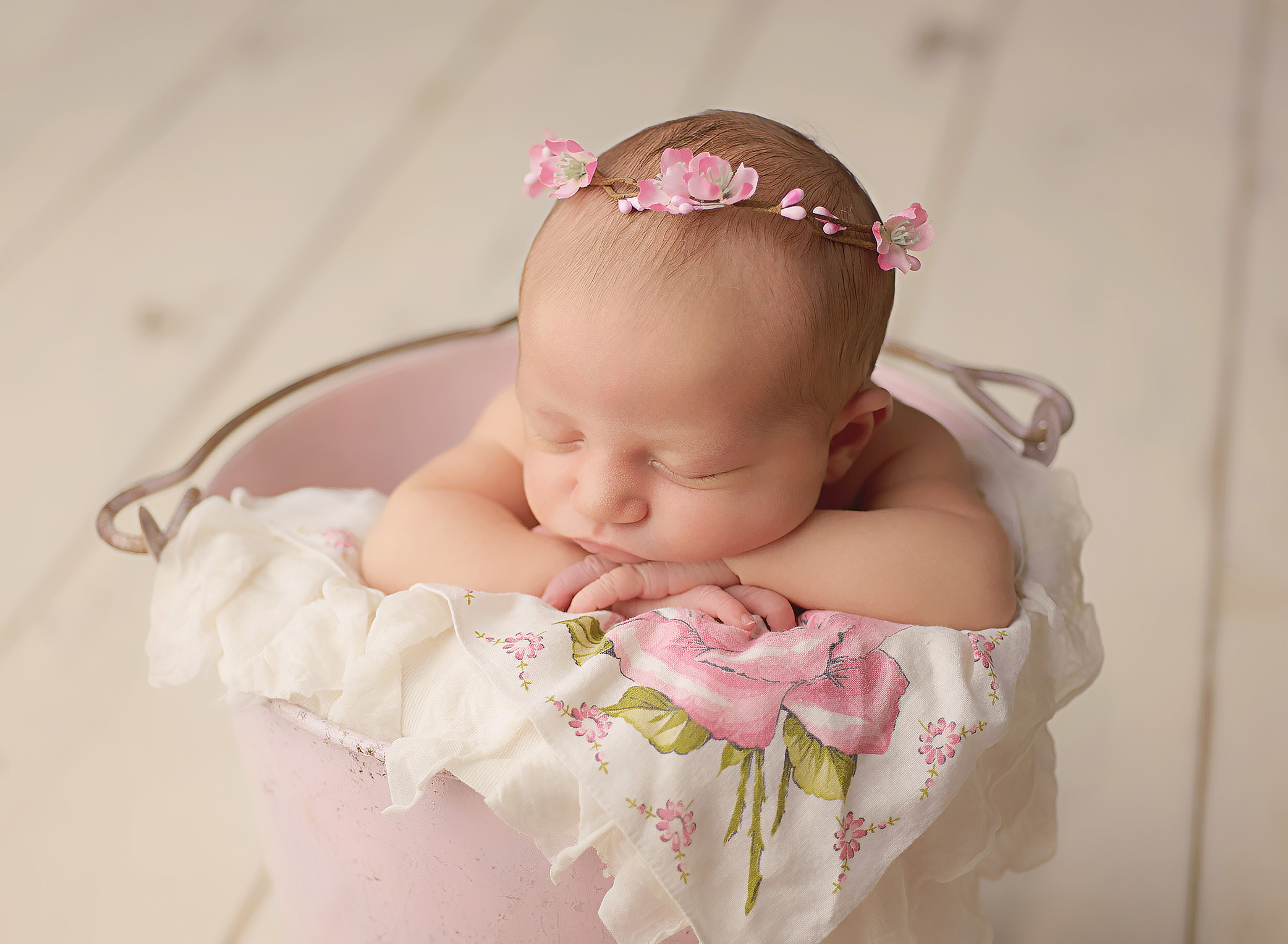 baby in pink bucket with floral crown