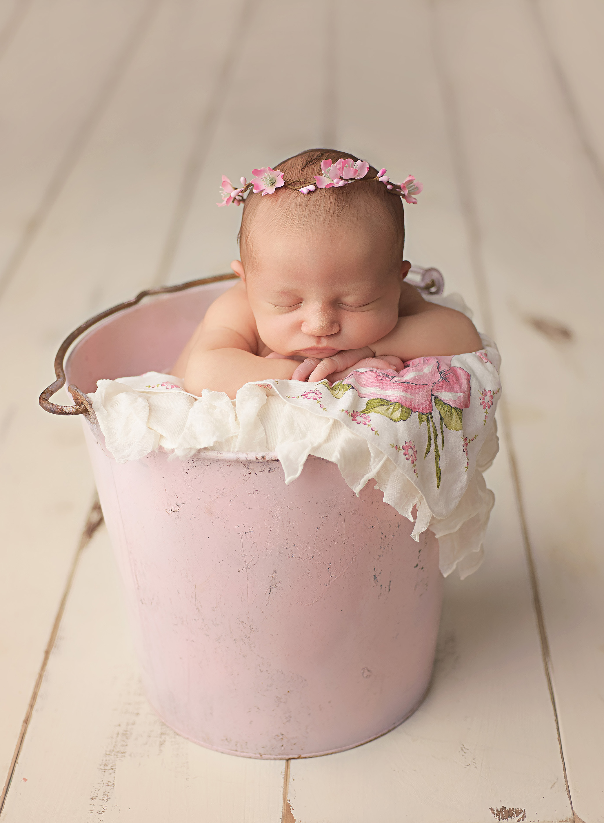 baby in pink bucket with floral crow