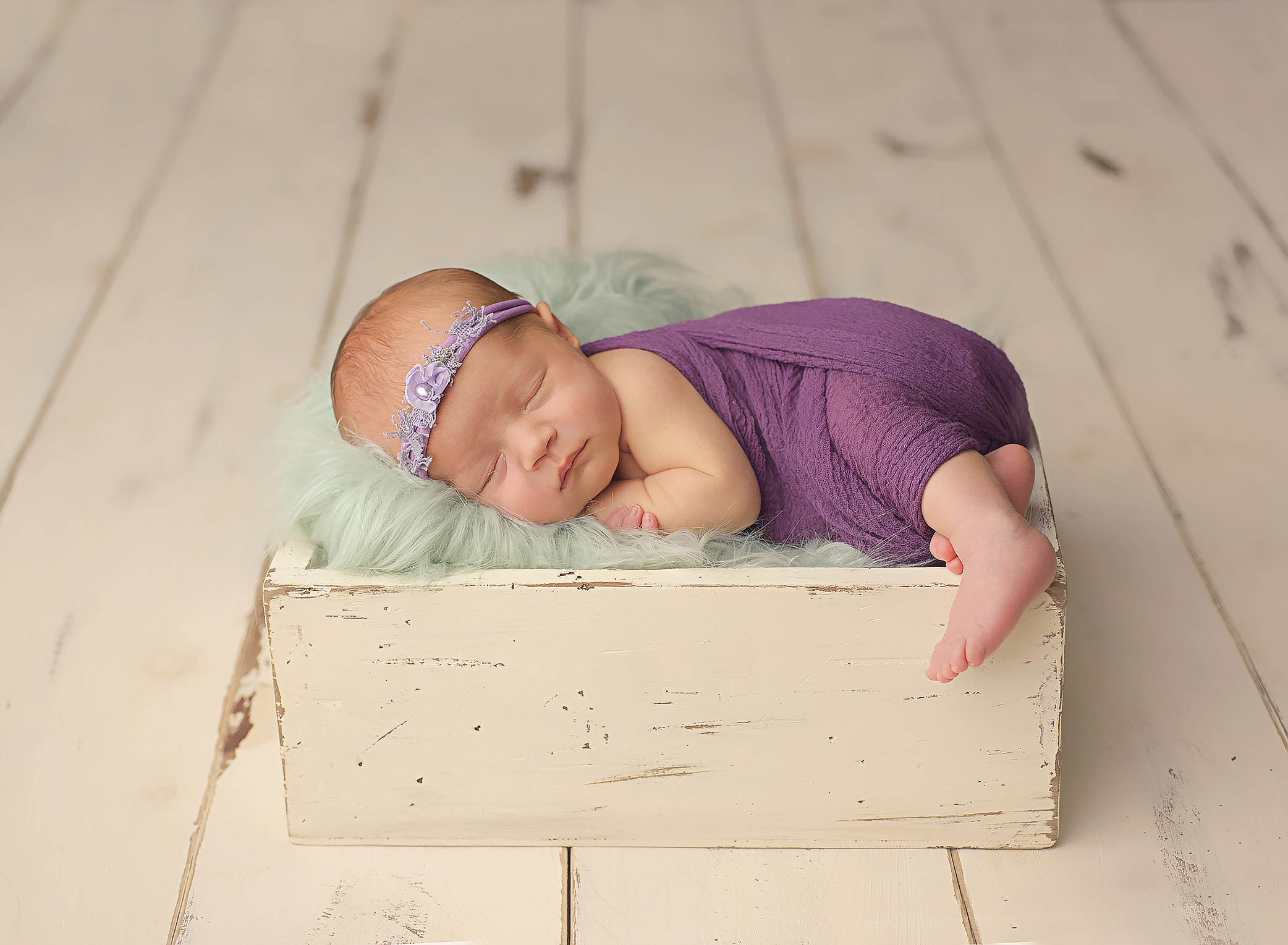 baby girl laying on her side in white wooden box