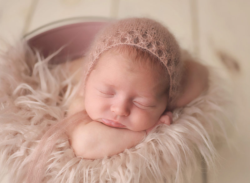 baby in mauve bucket with pink hat