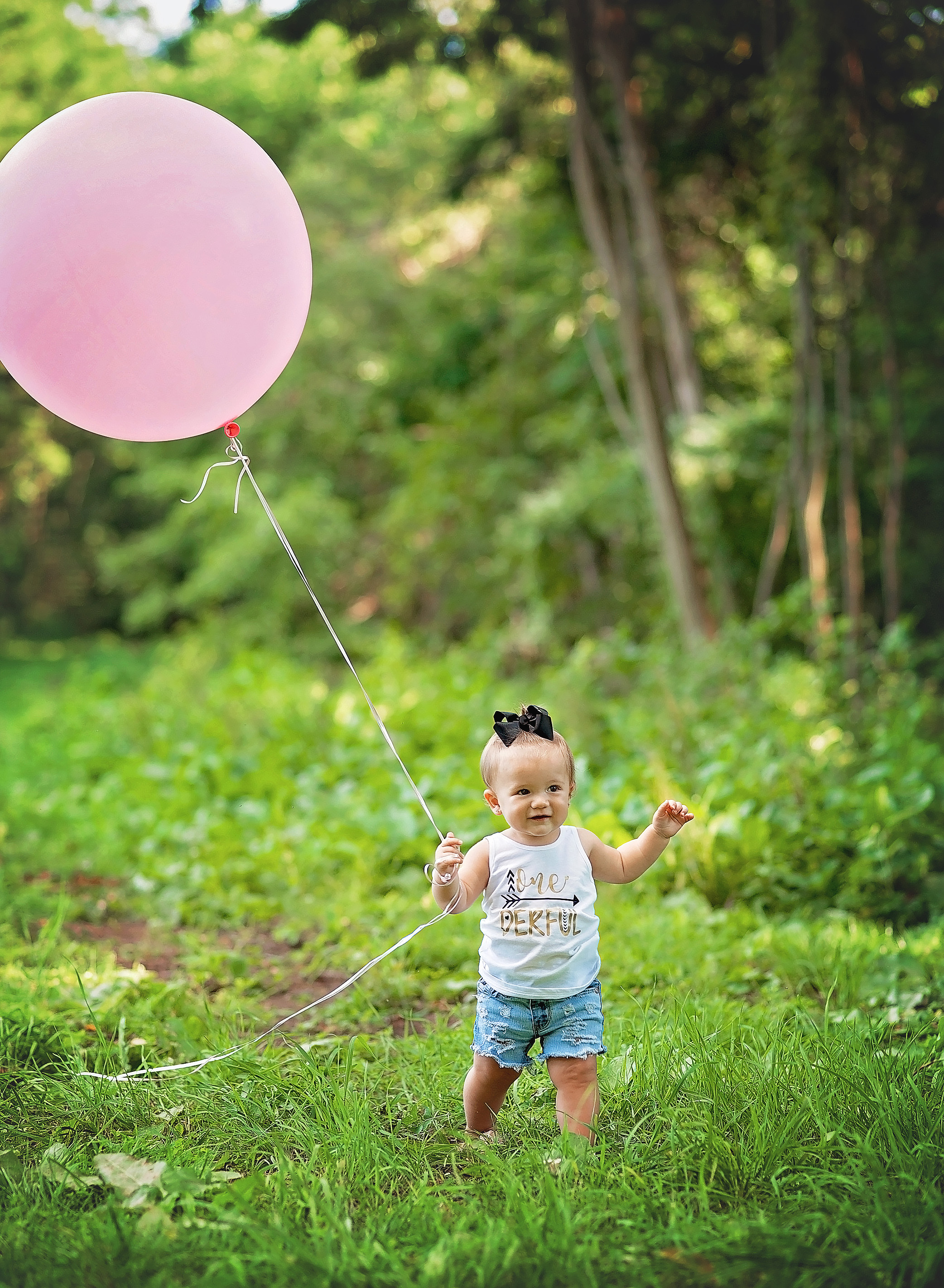 baby girl with large pink balloon