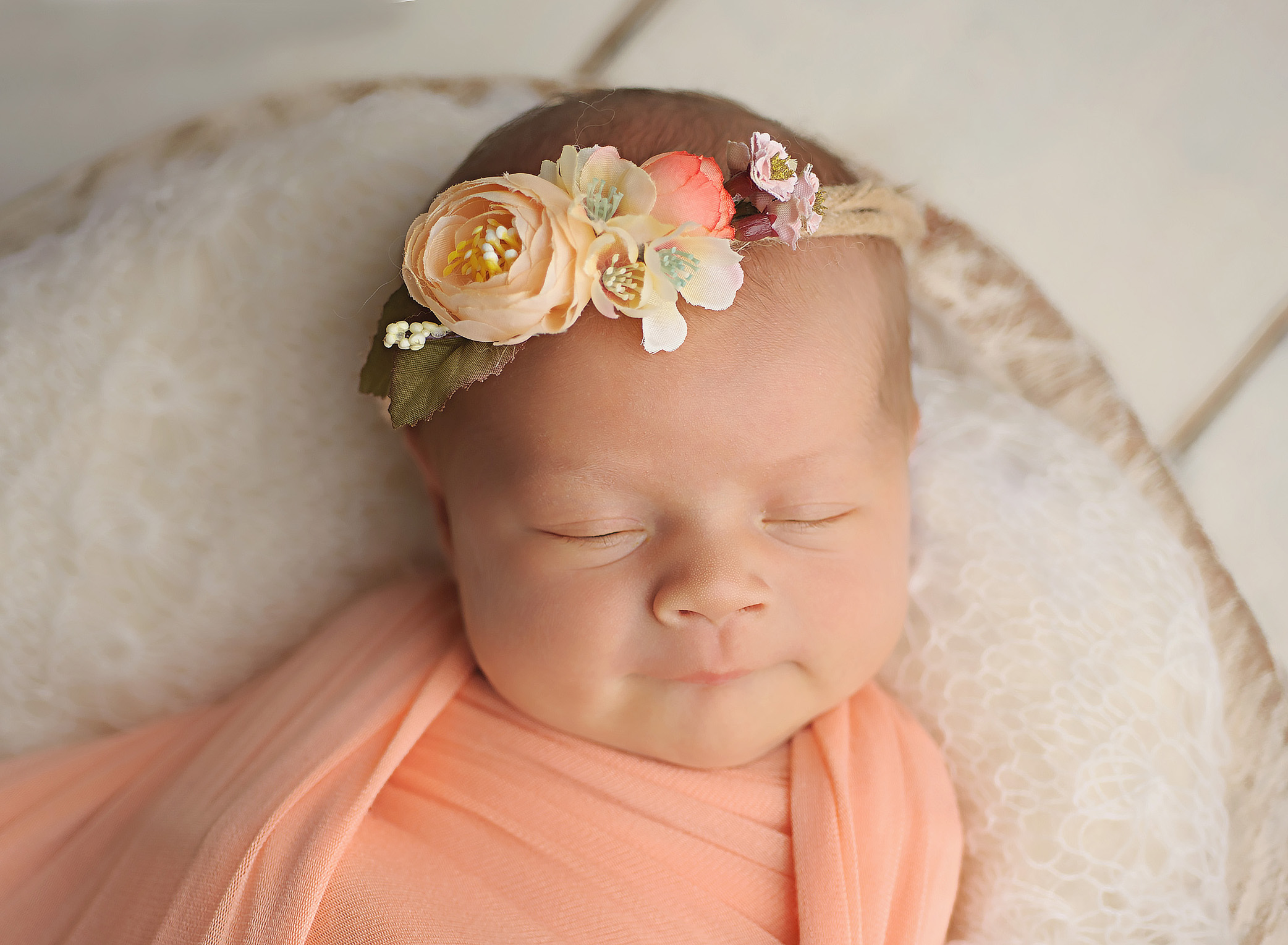 baby girl wrpped in peach with floral crown