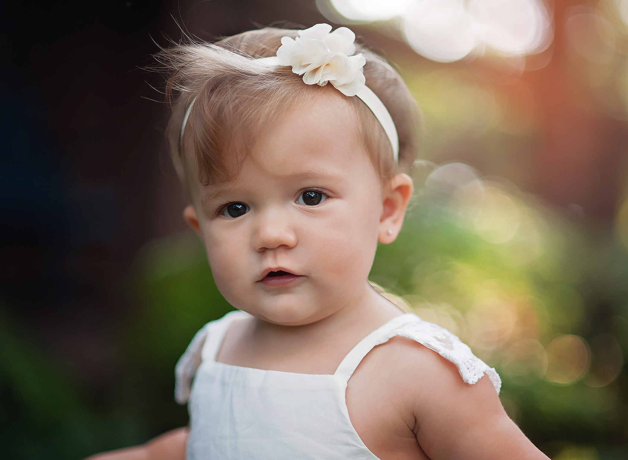 closeup of baby girl in white dress