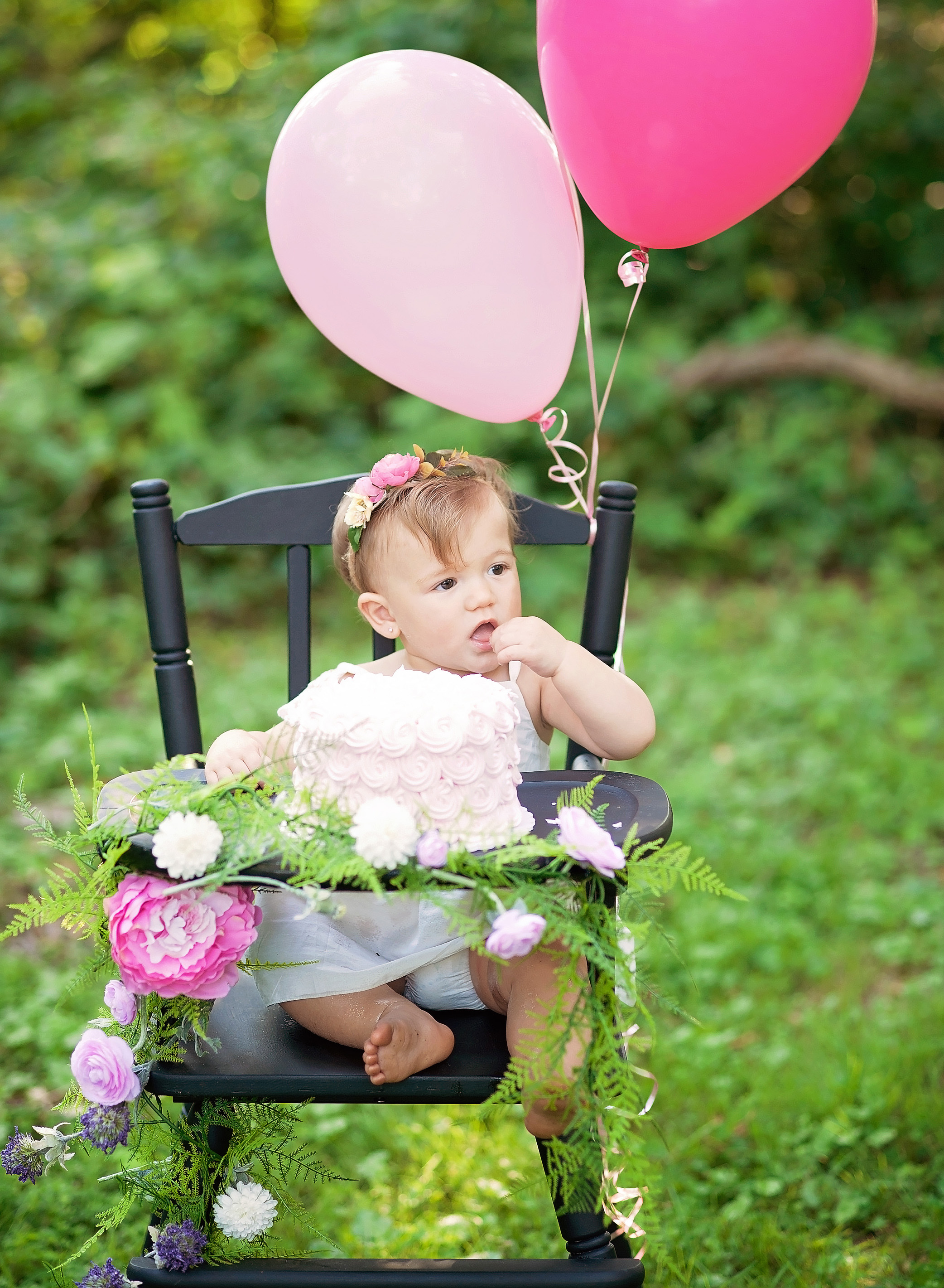baby girl in high chair with pink cake and balloons