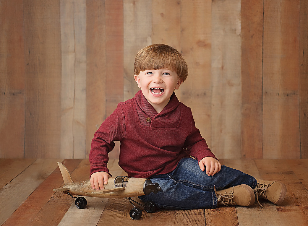3 year old boy smiling on wooden backdrop