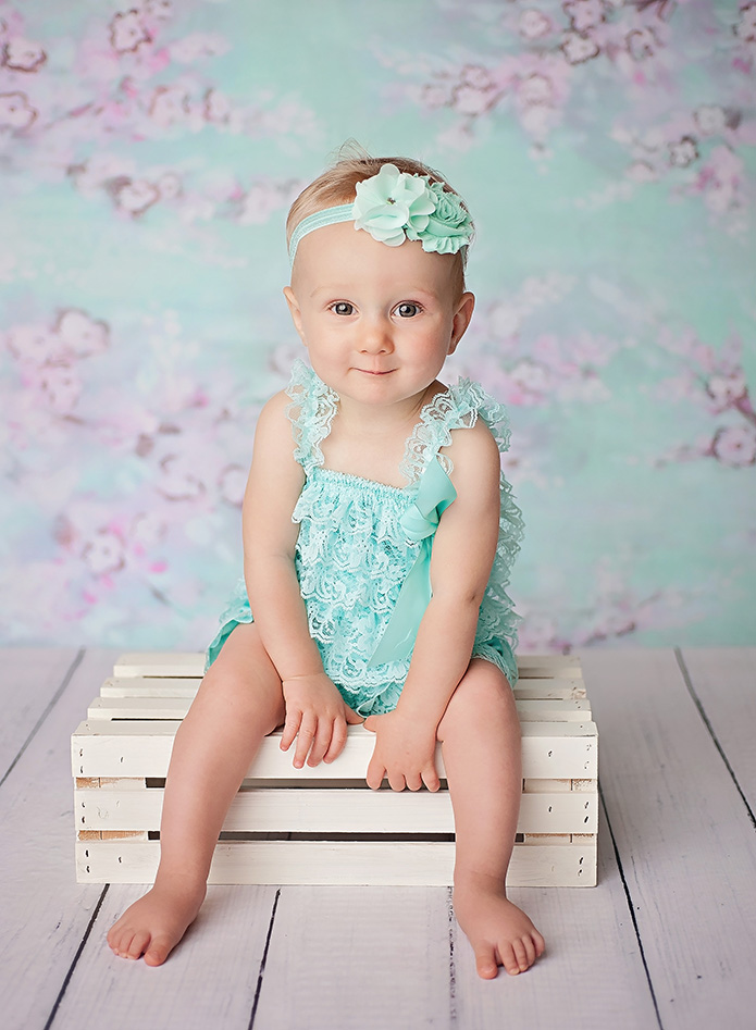 one year old girl sitting on white crate