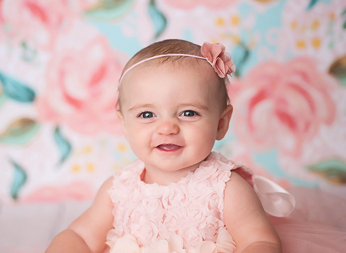 closeup of 6 month old baby girl in pink party dress against blue and pink backdrop