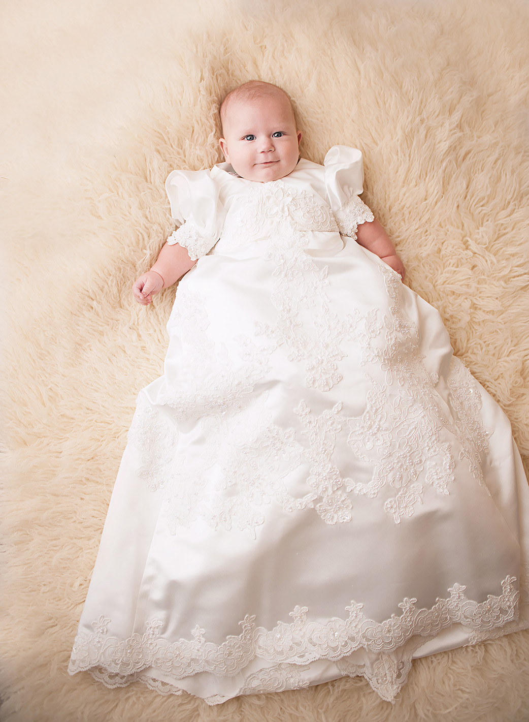 baby boy in baptism gown on white fur rug