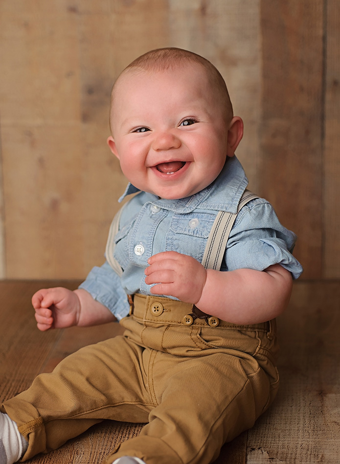 smiling 6 month old boy in suspenders