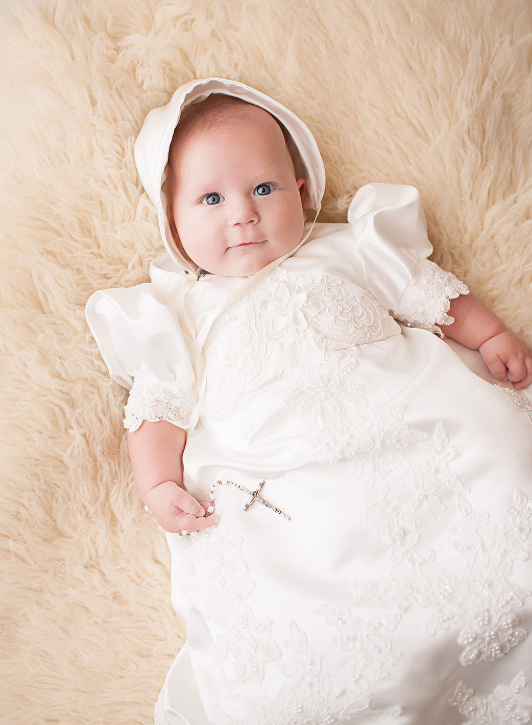 baby boy in baptism gown with rosary