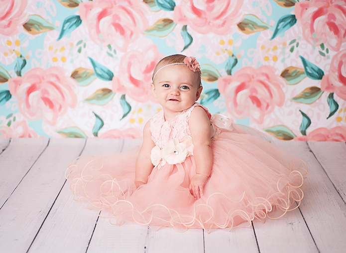6 month old baby girl in pink party dress against blue and pink backdrop