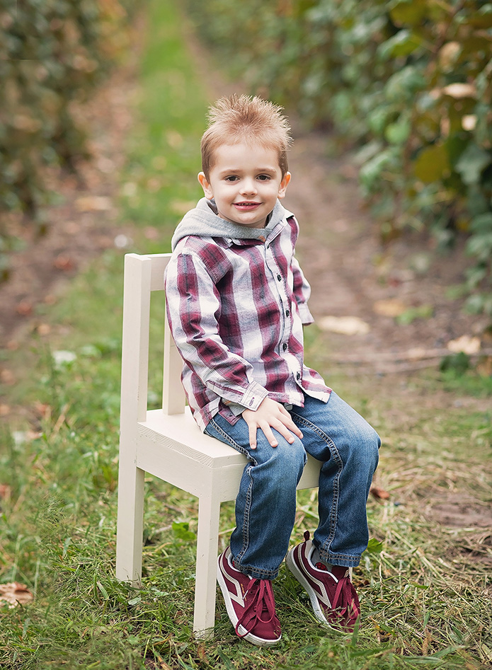 boy sitting on chair in grape vineyard