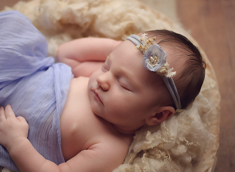 baby laying in white bowl with purple headband