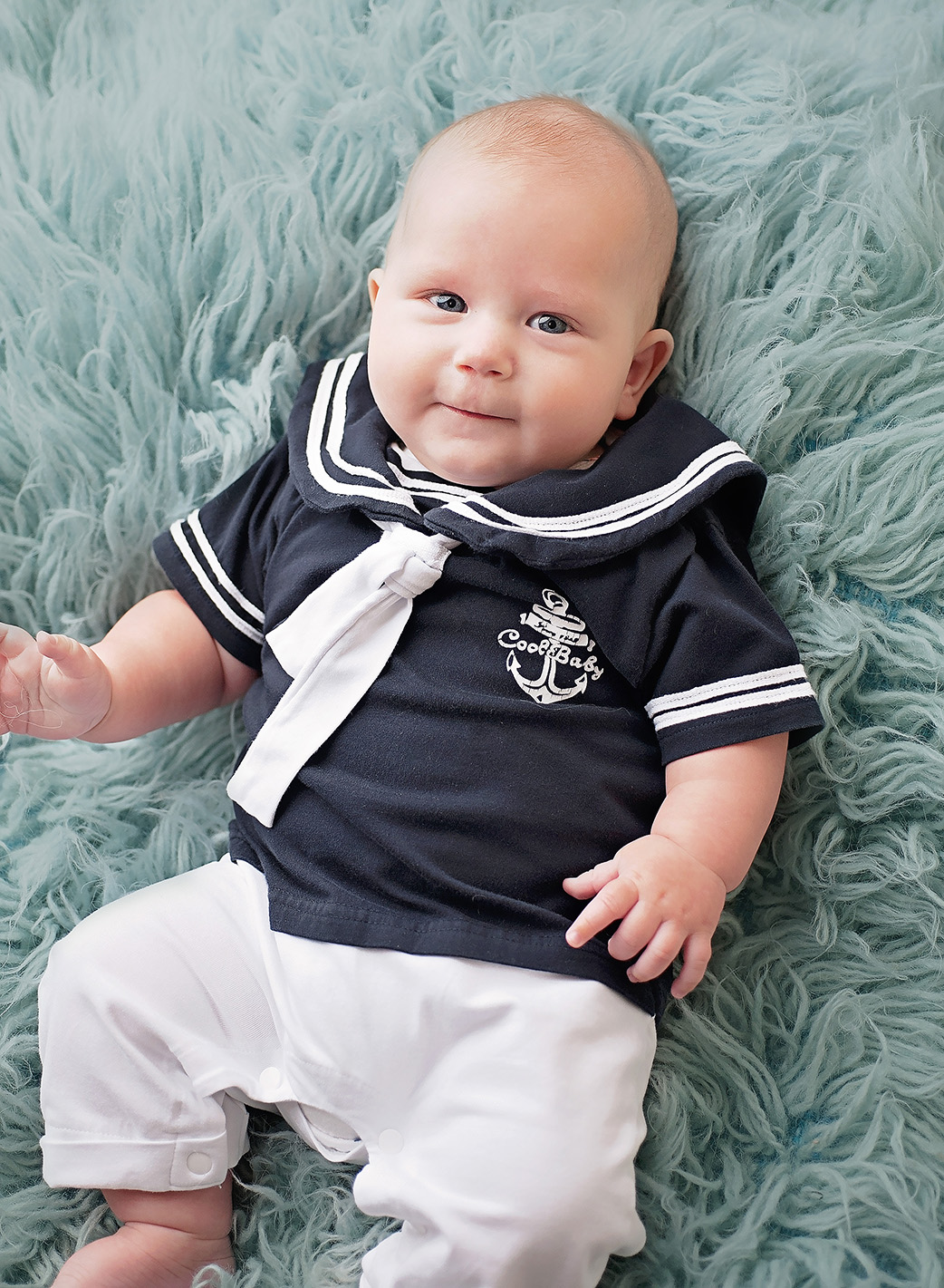 baby boy in sailor outfit on blue fur rug