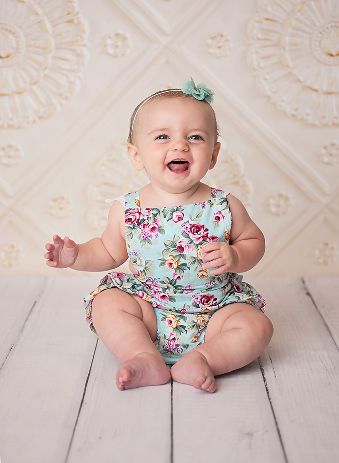 baby girl laughing against white tile backdrop