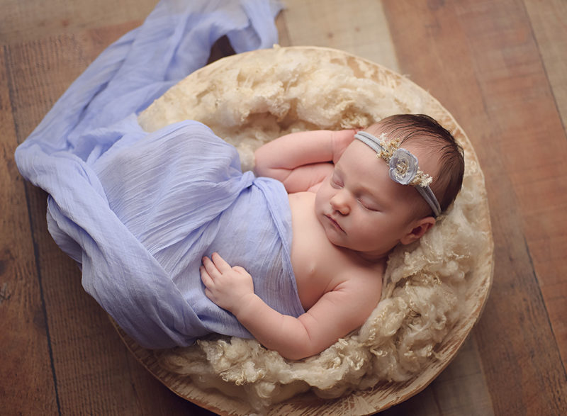 baby laying in wood bowl wrapped in purple fabric