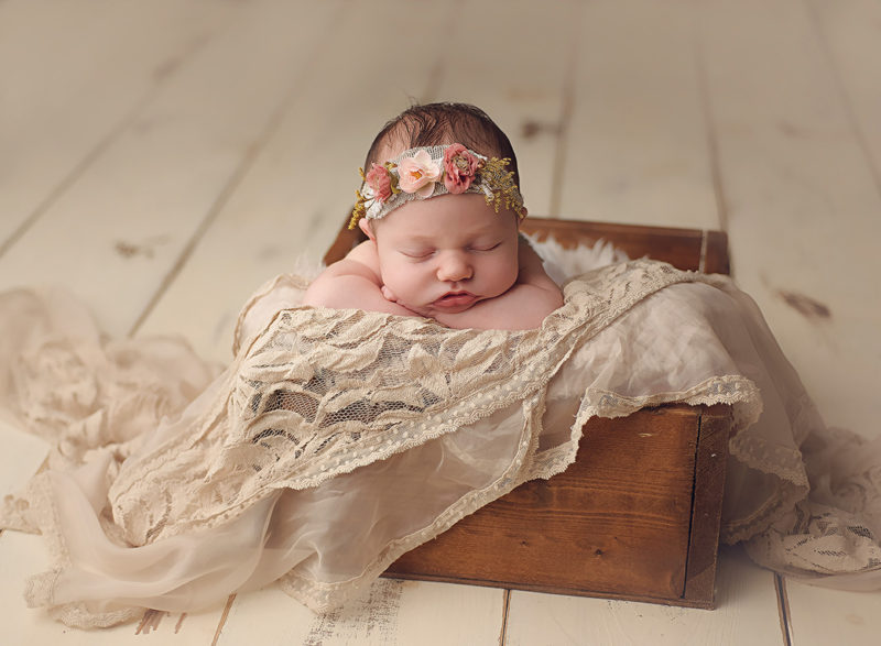 newborn baby in wooden box with floral headband