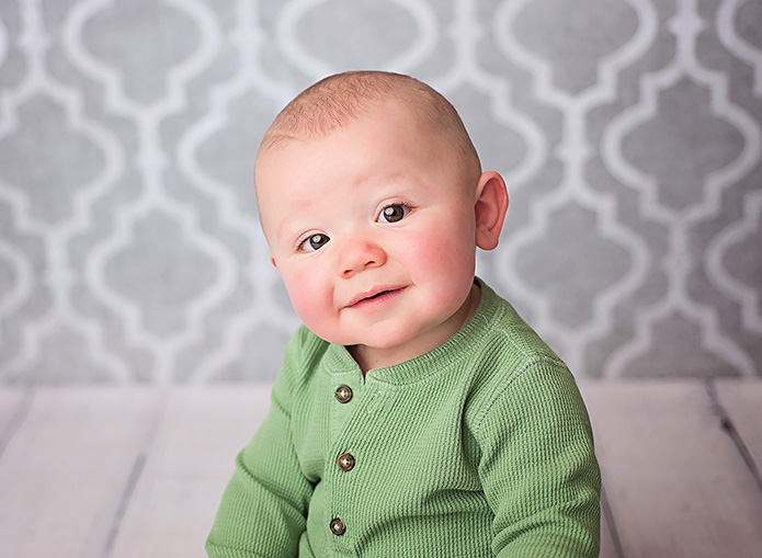 baby boy in green shirt against grey backdrop