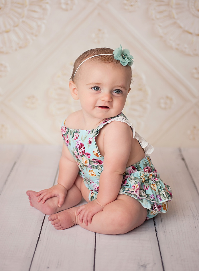 smiling baby girl in blue romper