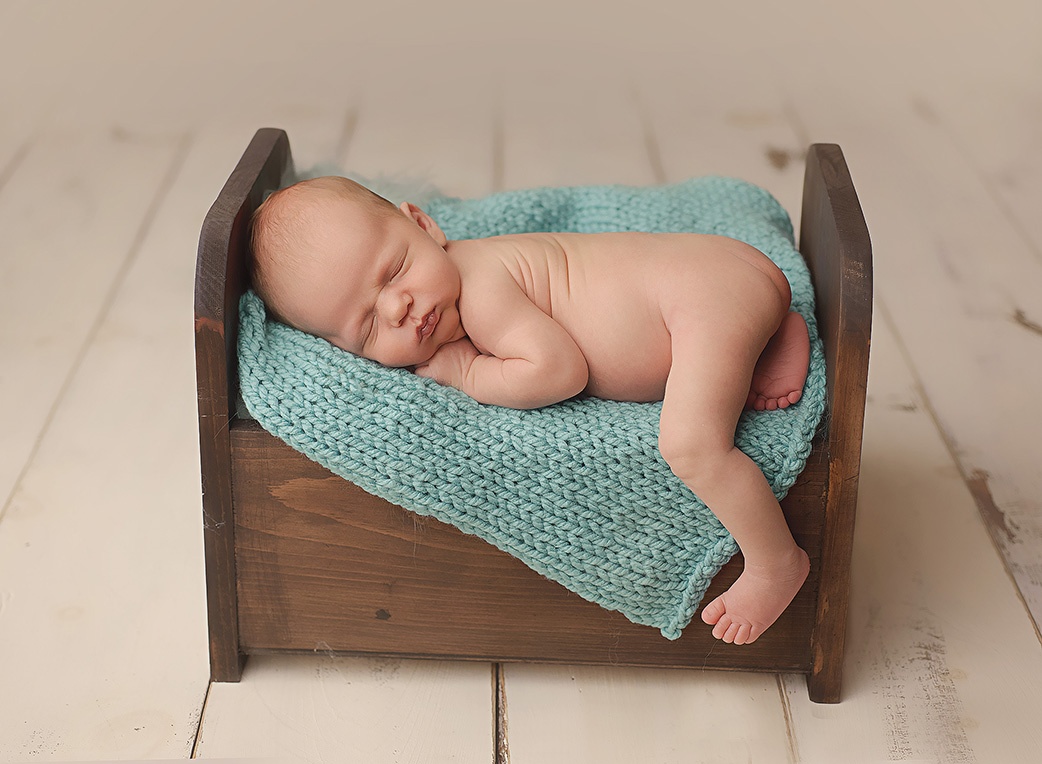 baby laying in wooden bed