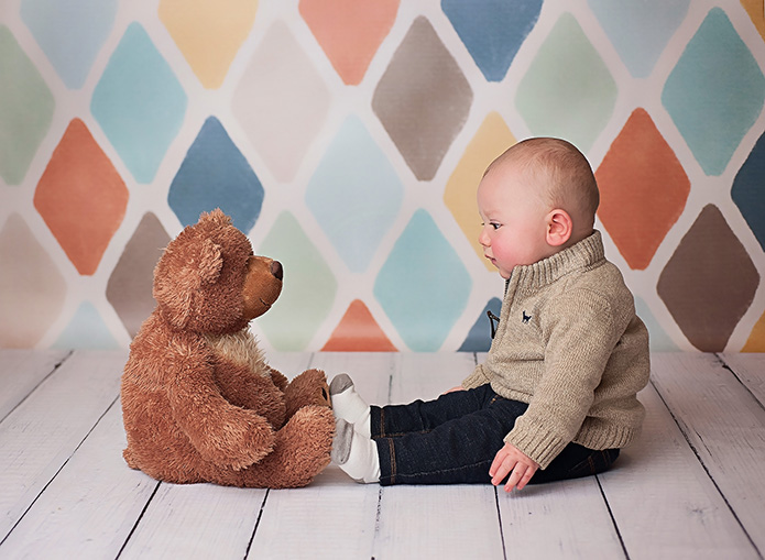 6 month old baby boy sitting with brown teddy bear