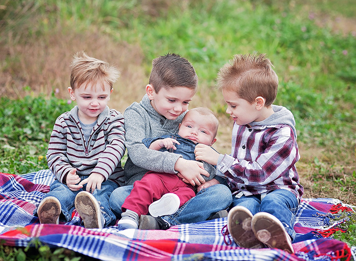 4 brothers on red and blue blanket playing with baby brother